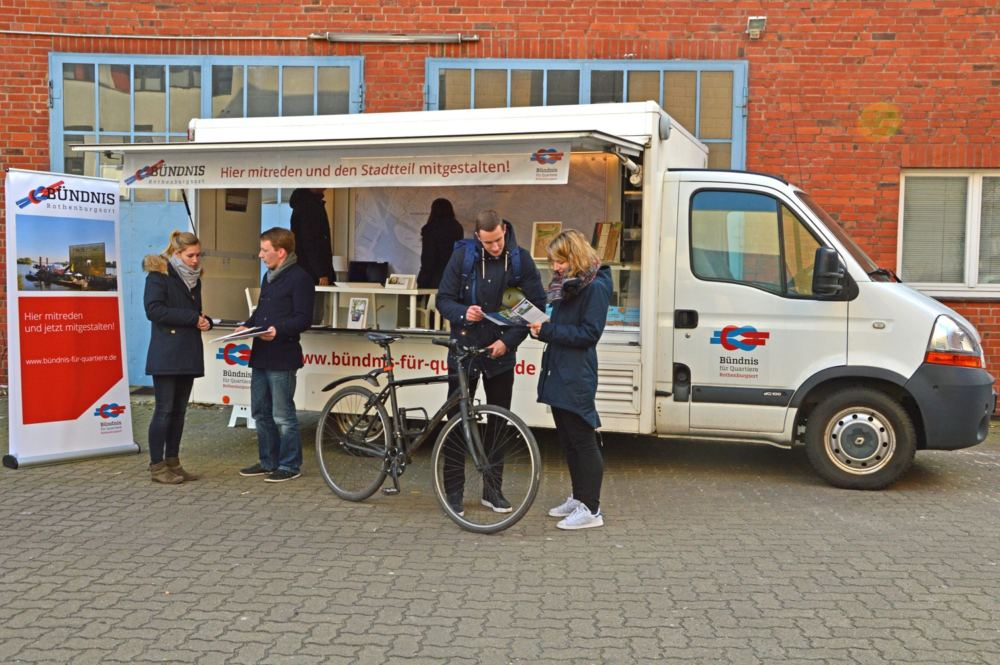 Infomobil zur Quartiersentwicklung. Weißer Lieferwagen als Informationsstand, davor reden Menschen miteinander.