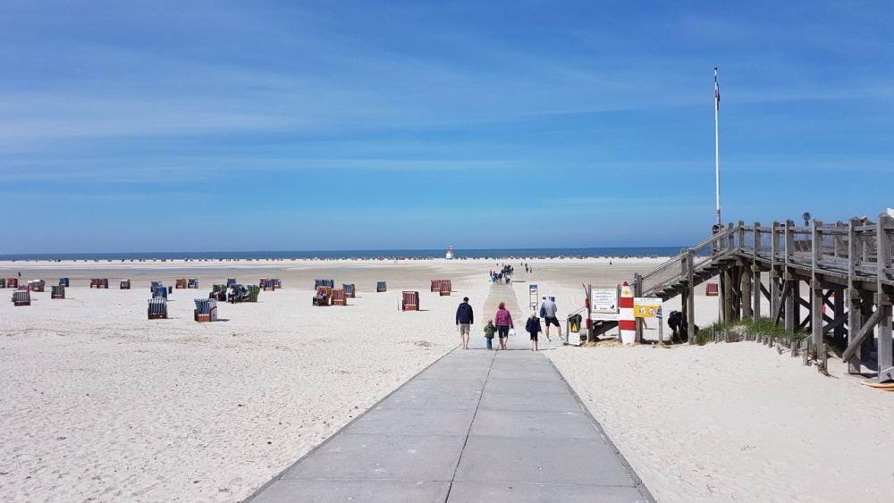 Menschen gehen auf dem Bohlenweg an den Strand in Norddorf auf Amrum.