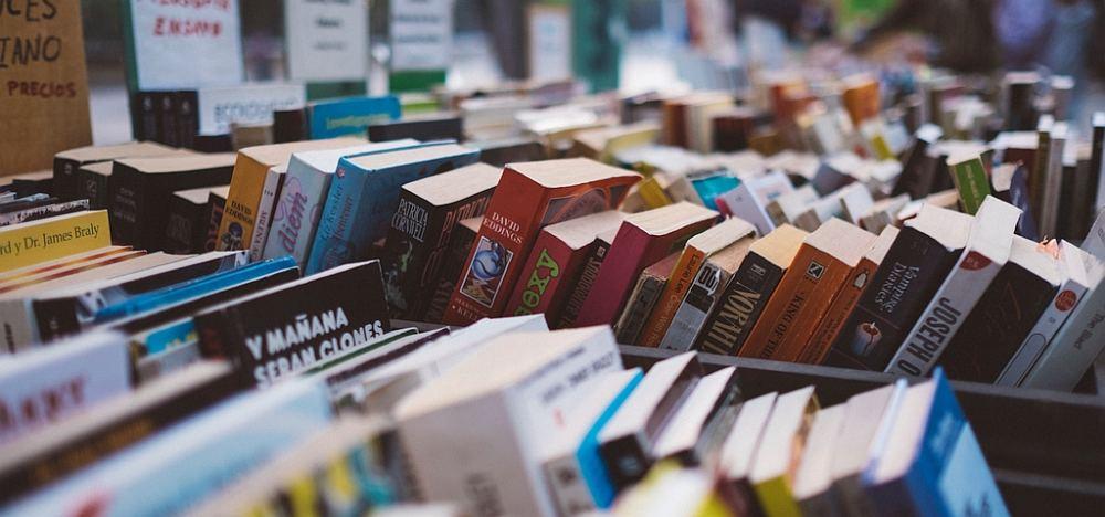 Kisten mit vielen bunten gebrauchten Büchern.