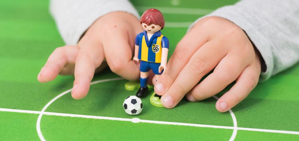 Kinderhände spielen Tischfußball
