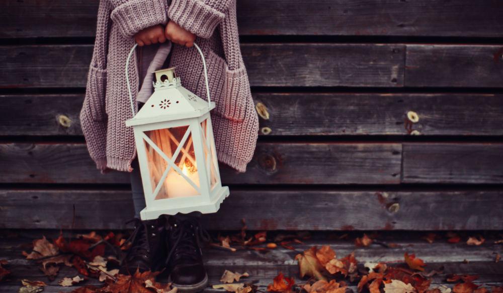 Ein Kind hält eine Laterne mit einer brennenden Kerze