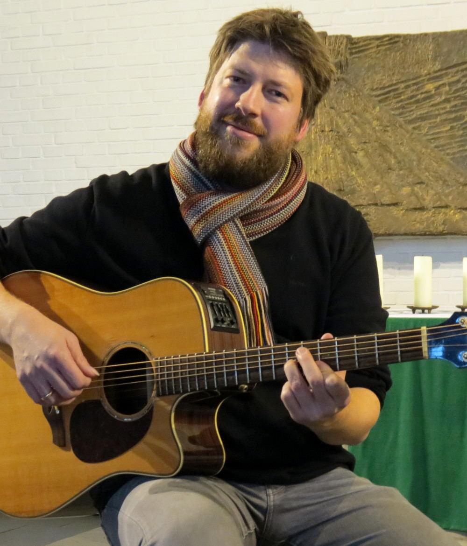 Der Popularkirchenmusiker Jan Keßler sitzt mit seiner Gitarre vor dem Altar