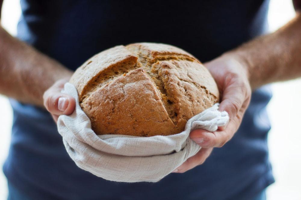 Hände halten ein frisches Brot. Die Krume ist kreuzförmig eingeschnitten.