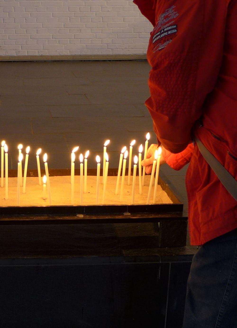 Person zündet eine Kerze im Kerzenbecken an