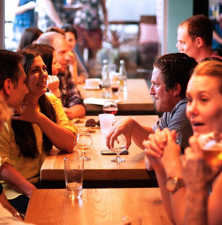 Freunde sitzen an einem Tisch - lebhaft in Gespräche vertieft.