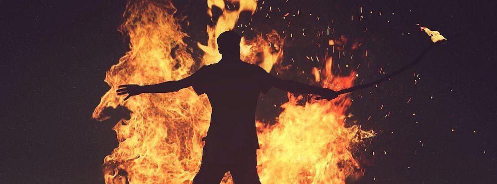 Mann steht mit ausgebreiteten Armen vor einem Feuer