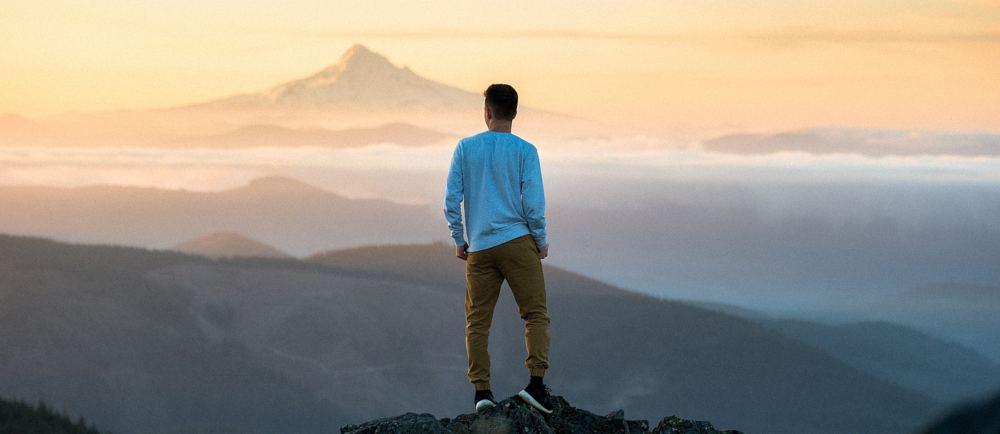 Ein junger Mann steht auf einem Gipfel und schaut auf das Bergpanorama im goldenen Abendlicht.