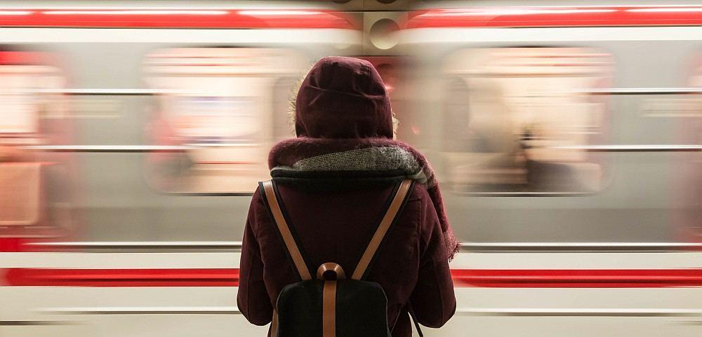 Mädchen mit Rucksartet wartet auf dem Bahnsteig - U-Bahn saust vorbei